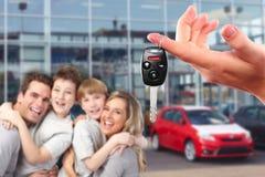 Lycklig familj med nya tangenter för en bil. Royaltyfri Fotografi
