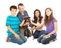 Lycklig familj med räddningsaktionhunden Royaltyfri Fotografi
