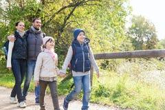 Lycklig familj med ryggsäckar som fotvandrar i trän Royaltyfria Bilder