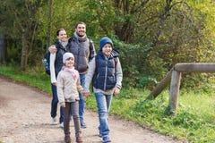 Lycklig familj med ryggsäckar som fotvandrar i trän Royaltyfri Fotografi