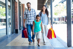 Lycklig familj med shoppingpåsar arkivfoto