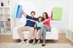 Lycklig familj med shoppingpåsar hemma Fotografering för Bildbyråer