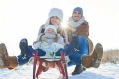Lycklig familj med släden i vinter royaltyfri fotografi