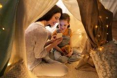 Lycklig familj med smartphonen i ungetält hemma arkivfoton
