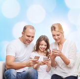 Lycklig familj med smartphones Royaltyfria Bilder
