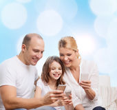 Lycklig familj med smartphones Arkivfoton