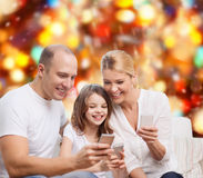 Lycklig familj med smartphones Arkivbilder