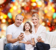 Lycklig familj med smartphones Fotografering för Bildbyråer