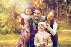Lycklig familj med smartphoneselfiepinnen i trän Royaltyfri Bild