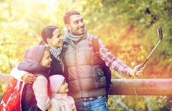 Lycklig familj med smartphoneselfiepinnen i trän Arkivfoto