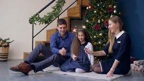 Lycklig familj med tomtebloss som firar jul arkivfilmer