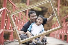 Lycklig familj med träramen royaltyfria bilder
