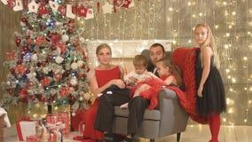 Lycklig familj med tre barn som sitter vid julgranen arkivfilmer