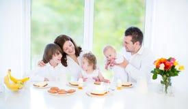 Lycklig familj med tre barn som tycker om frukosten fotografering för bildbyråer