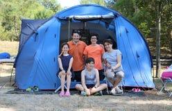 Lycklig familj med tre le barn och tält i koloni Royaltyfri Bild