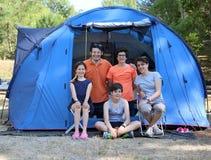 Lycklig familj med tre le barn och tält i koloni Royaltyfri Foto