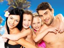 Lycklig familj med två barn på den tropiska stranden royaltyfri fotografi