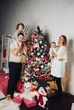 Lycklig familj med två barn på julgranen arkivbild