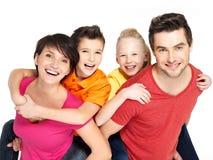 Lycklig familj med två barn på vit Fotografering för Bildbyråer