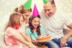 Lycklig familj med två ungar i partihattar hemma Arkivfoto