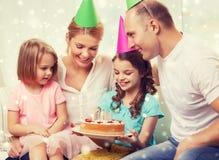 Lycklig familj med två ungar i partihattar hemma Royaltyfria Bilder