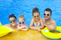 Lycklig familj med två ungar som har gyckel i simbassängen royaltyfria bilder