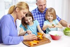 Lycklig familj med två ungar som hemma lagar mat Arkivbild