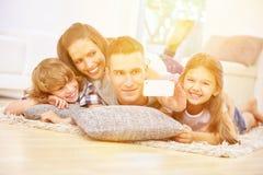 Lycklig familj med två ungar som tar selfie arkivbild