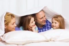 Lycklig familj med två ungar under filten hemma Arkivbild