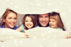Lycklig familj med två ungar under filten hemma arkivfoto