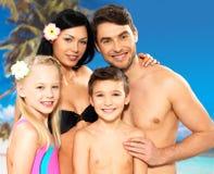 Lycklig familj med två barn på den tropiska stranden Royaltyfri Bild