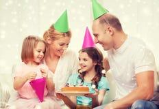 Lycklig familj med två ungar i partihattar hemma Royaltyfri Fotografi