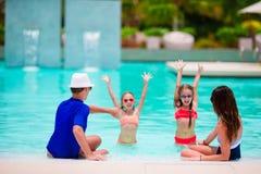 Lycklig familj med två ungar i simbassäng Royaltyfria Foton