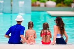 Lycklig familj med två ungar i simbassäng Arkivfoto