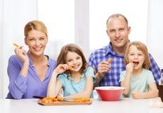 Lycklig familj med två ungar som hemma äter Arkivfoton