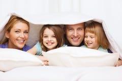 Lycklig familj med två ungar under filten hemma Arkivbilder