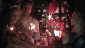 Lycklig familj med unga ungar som in tänder tomtebloss stock video
