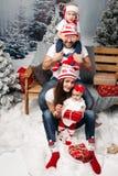 Lycklig familj med ungar på jultid arkivfoto