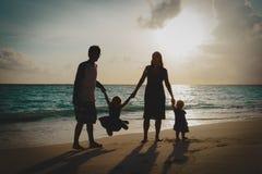 Lycklig familj med ungar på lek på solnedgångstranden royaltyfria bilder