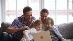 Lycklig familj med ungar som har gyckel genom att använda bärbara datorn tillsammans arkivfilmer