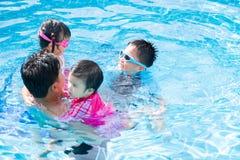 Lycklig familj med ungar som har gyckel i simbassäng arkivfoto