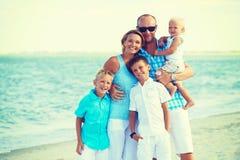 Lycklig familj med ungar som står på stranden Arkivbilder