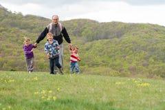 Lycklig familj med ungar som tycker om fri tid på naturlig backg Arkivfoto