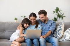 Lycklig familj med ungeflickan som har gyckel genom att använda bärbara datorn tillsammans royaltyfria foton