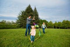 lycklig familj Moder fader, barn som kör över en grön mjöd fotografering för bildbyråer