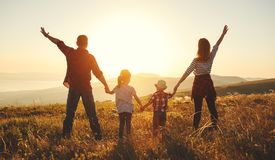 Lycklig familj: moder, fader, barn son och dotter på solnedgång arkivfoto