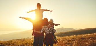 Lycklig familj: moder, fader, barn son och dotter på solnedgång arkivbilder