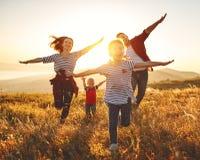 Lycklig familj: moder, fader, barn son och dotter på solnedgång royaltyfri bild