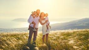 Lycklig familj: moder, fader, barn son och dotter på sunse arkivfoton