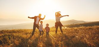 Lycklig familj: moder, fader, barn son och dotter på sunse royaltyfri foto